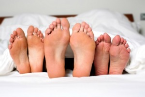 Humorous image of the bare feet of a man and two women in bed sticking out from under the bedclothes conceptual of a threesome, orgy, swingers or sexual cheating